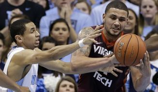 North Carolina's Marcus Paige, left, reaches in on Virginia Tech's Malik Muller during the first half of an NCAA college basketball game in Chapel Hill, N.C., Sunday, Jan. 18, 2015. (AP Photo/Gerry Broome)