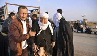 In this photo taken on Saturday, Jan. 17, 2015, a man helps an elderly Yazidi woman after Yazidis were released by Islamic militants, as they arrive in Kirkuk, 180 miles (290 kilometers) north of Baghdad, Iraq. The Islamic State group released about 200 Yazidis held for five months in Iraq, mostly elderly, infirm captives who likely slowed the extremists down, Kurdish military officials said Sunday. Almost all of the freed prisoners are in poor health and bore signs of abuse and neglect. (AP Photo)