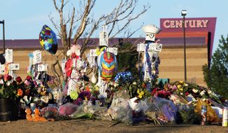 In this July 27, 2012, file photo, crosses, flowers and other mementos of the victims of the Aurora, Colo., movie theater shooting are shown at sunrise with the movie theater in the background. (AP Photo/Ted S. Warren, File)