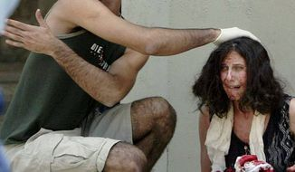 In this July 31, 2002, file photo, a man helps a wounded woman near the scene of an explosion at the Hebrew University in Jerusalem where a bomb exploded in the crowded cafeteria that killed nine people and wounded more than 70. Testimony opened in the week of Jan. 12, 2015, for a $1 billion lawsuit brought by U.S. terrorism victims against the Palestinian Authority and the Palestine Liberation Organization. The case is one of three major cases proceeding through New York federal courts under the Anti-Terrorism Act: a federal law letting victims of terrorism seek compensation. (AP Photo/David Guttenfelder, File)
