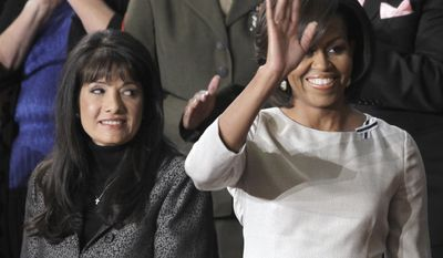 Kathy Proctor of Winston-Salem, N.C., applauds at left, as first lady Michelle Obama waves on Capitol Hill in Washington, Tuesday, Jan. 25, 2011, during President Barack Obama's State of the Union address.  (AP Photo/Charles Dharapak)