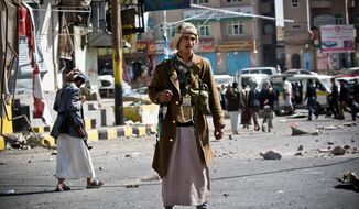 Houthi Shiite Yemeni gather Tuesday while guarding a street leading to the presidential palace in Sanaa, Yemen. (Associated Press)