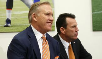 John Elway, left, Denver Broncos general manager and executive vice president of football operations, smiles before introducing Gary Kubiak, right, as the new head coach of the Broncos during am NFL football news conference, Tuesday, Jan. 20, 2015, in Englewood, Colo. (AP Photo/Jack Dempsey)