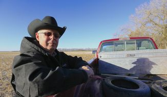 In this Jan. 16, 2015, file photo, Ken Prososki, who opposes the Keystone XL pipeline, leans against his pickup along the route of the pipeline, which is planned to go through his property, in Fullerton, Neb.  (AP Photo/Nati Harnik, File)