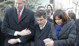 New York city mayor Bill de Blasio, left, Paris mayor Anne Hidalgo, right, and Patrick Pelloux, center, a staff member of Charlie Hebdo newspaper, react outside Charlie Hebdo offices, in Paris, Tuesday Jan. 20, 2015. Brothers Said and Cherif Kouachi and their friend, Amedy Coulibaly, killed 17 people at the satirical newspaper Charlie Hebdo, a kosher grocery and elsewhere last week. (AP Photo/Francois Mori)