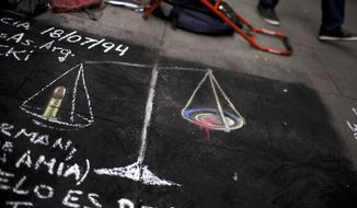 A drawing asking for justice in Argentina, of the scales of justice, with a bullet on one side and blood on the other is seen on a sidewalk in Buenos Aires, Argentina, Tuesday, Jan. 20, 2015. Special prosecutor Alberto Nisman, who had been investigating the 1994 bombing of the AMIA Jewish community center in Buenos Aires that killed 85 people and who accused President Cristina Fernandez of shielding Iranian suspects, was found dead from a gun shot to the head in his apartment late Sunday, hours before he was to testify in a congressional hearing about the case. (AP Photo/Rodrigo Abd)