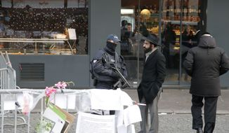 A police officer talks to Jewish man outside the kosher grocery where Amedy Coulibaly killed four people in a terror attack in Paris last week, in this Jan. 20, 2015, photo. (AP Photo/Francois Mori)