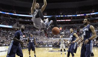 Georgetown forward Isaac Copeland (11) dunks in front of Villanova forward JayVaughn Pinkston (22) and guard Darrun Hilliard II (4)  during the second half of an NCAA college basketball game, Monday, Jan. 19, 2015, in Washington. Copeland had 17 points. Georgetown won 78-58. (AP Photo/Alex Brandon)