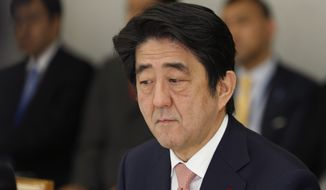 Japan's Prime Minister Shinzo Abe reacts at a meeting on two Japanese hostages taken by the Islamic State group, at the prime minister's official residence in Tokyo on Wednesday, Jan. 21, 2015. (AP Photo/Shizuo Kambayashi, Pool)