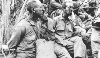 U.S. prisoners of war sit with their hands tied behind their backs during the Bataan Death March during World War II. (Image: U.S. Air Force)