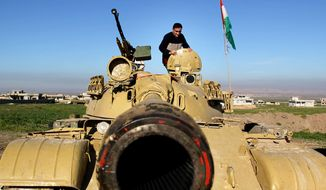 A Kurdish peshmerga stands on a military tank preparing for battle against the Islamic State group in northern Iraq, Jan. 20, 2015. (Associated Press) ** FILE **