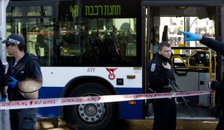 "Israeli police officers secure the scene of a stabbing attack in Tel Aviv, Israel, Wednesday, Jan. 21, 2015. A Palestinian man stabbed nine people, injuring several seriously, on a bus in central Tel Aviv before he was chased down, shot and arrested, Israeli police said Wednesday, describing the assault as a ""terror attack"" in the latest in a spate of violence, the worst Israel has seen in almost a decade. (AP Photo/Oded Balilty)"