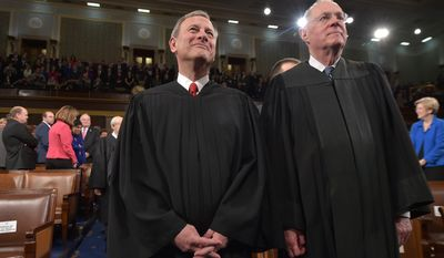 US Chief Justice  John G. Roberts and Supreme Court Justices Anthony M. Kennedy stand before US President Barack Obama's State Of The Union address on January 20, 2015 at the US Capitol in Washington, DC. AFP PHOTO/POOL/MANDEL NGAN