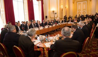 Ministers and government officials attend an international meeting on defeating the Islamic State militant group, a meeting hosted by British Foreign Secretary Philip Hammond at Lancaster House in London no Thursday, Jan. 22, 2015. (AP Photo/Stefan Rousseau/PA)