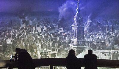 Visitors stand in front of the monumental panoramic artwork 'DRESDEN 1945', which is printed on cloth widths, of artist Yadegar Asisi during a press preview at the Dresden Asisi Panometer in Dresden, Germany, Friday, Jan. 23, 2015. The picture shows the destroyed city of Dresden after the bombing raids during the World War II in February 1945. (AP Photo/Jens Meyer)