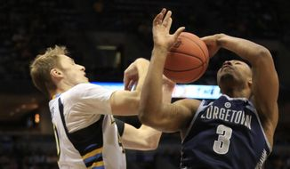 Marquette center Luke Fischer, left, fouls Georgetown forward Mikael Hopkins, right, during the second half of an NCAA college basketball game Saturday, Jan. 24, 2015, in Milwaukee. (AP Photo/Darren Hauck)