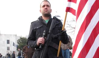 Arin Forrest of Portland, Ore.,  holds an AR-15 rifle at a pro-gun rally outside the state Capitol in Salem, Ore. (Associated Press)
