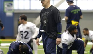 Seattle Seahawks defensive coordinator Dan Quinn, center, walks on the field as players stretch Friday, Jan. 23, 2015, during NFL football practice in Renton, Wash. The Seahawks are to face the New England Patriots in Super Bowl XLIX on Sunday, Feb. 1, 2015, in Glendale, Ariz. (AP Photo/Ted S. Warren)