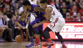 Northwestern guard JerShon Cobb, left, is pressured by Maryland guard Melo Trimble as he tries to control a loose ball in the second half of an NCAA college basketball game, Sunday, Jan. 25, 2015, in College Park, Md. Maryland won 68-67. (AP Photo/Patrick Semansky)