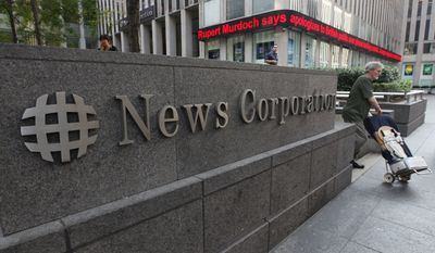 News about Rupert Murdoch is displayed on the Fox News ticker at a building which houses the News Corp. headquarters, Friday, July 15, 2011, in New York. Murdoch accepted the resignation of The Wall Street Journal's publisher and the chief of his British operations on Friday as the once-defiant media mogul struggled to control an escalating phone hacking scandal with apologies to the public and the family of a murdered schoolgirl. The controversy claimed its first victim in the United States as Les Hinton, chief executive of the Murdoch-owned Dow Jones & Co. and publisher of the Wall Street Journal, announced he was resigning, effective immediately. (AP Photo/Mary Altaffer)