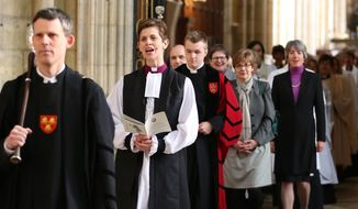 The Rev. Libby Lane, second left, arrives at York Minster, England, where she will be consecrated as the eighth Bishop of Stockport, Monday Jan. 26, 2015. Male domination in the leadership of the Church of England is coming to an end, as the 500-year-old institution consecrates its first female bishop. (AP Photo/PA, Lynne Cameron)