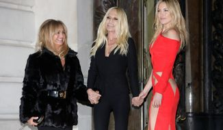 From left, Goldie Hawn, Italian fashion designer Donatella Versace and Kate Hudson pose as they arrive for the show of the Atelier Versace Spring-Summer 2015 Haute Couture fashion collection presented in Paris, France, Sunday, Jan. 25, 2015. (AP Photo/Thibault Camus)