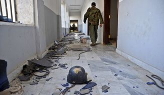 A Libyan military soldier walks past damage inside a building that was used by Islamic militias for fighting in Benghazi, Libya. (Associated Press) ** FILE **