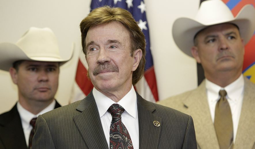 Actor Chuck Norris (center) looks on during a Dec. 2, 2010, ceremony in Garland, Texas, where he was made an honorary Texas Ranger. (Associated Press) **FILE**