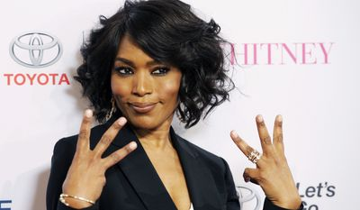 """Actress Angela Bassett, making her directorial debut with the Lifetime film """"Whitney,"""" poses for photographers at the premiere of the film at the Paley Center for Media on Tuesday, Jan. 6, 2015, in Beverly Hills, Calif. (Photo by Chris Pizzello/Invision/AP)"""