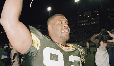 Green Bay Packers' Reggie White plays to the crowd following the Packers 30-27 win over the Denver Broncos in Green Bay, Wisconsin, Oct. 10, 1993. White sacked Broncos quarterback John Elway twice in a row to end the Broncos final drive of the game. White had a total of three sacks in the game. (AP Photo/Roberto Borea)