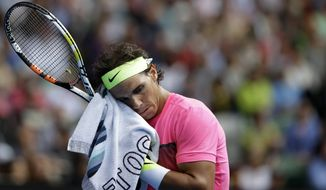Rafael Nadal of Spain wipes the sweat from the face as he plays Tomas Berdych of the Czech Republic during their quarterfinal match at the Australian Open tennis championship in Melbourne, Australia, Tuesday, Jan. 27, 2015. (AP Photo/Bernat Armangue)