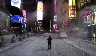 A pedestrian walks in the middle of Seventh Avenue in Times Square, New York, early Tuesday, Jan. 27, 2015.  (AP Photo/Seth Wenig)