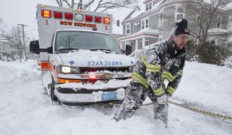 New Bedford firefighter Lt. Eric Hartford tries to dig out an ambulance carrying a patient en route to St. Lukes Hospital in New Bedford, Mass., on Tuesday, Jan. 27, 2015, as the region digs itself out of the snow storm that covered the area. The nor'easter was predicted to continue to pound Connecticut, Rhode Island, Massachusetts, New Hampshire and Maine with snow and wind through Tuesday. Total accumulation was expected to reach or exceed two feet in most of Massachusetts, potentially making it one of the top snowstorms of all time. (AP Photo/The Standard-Times, Peter Pereira)