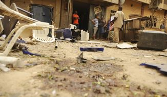 People stand near blood stains in the street following last night's explosion in Kano, Nigeria, Monday, May 19, 2014. A car bomb exploded in the Christian neighborhood of Nigeria's second most populous and mainly Muslim city of Kano on Sunday night, killing at least four people, police said. Five people were wounded. Police Superintendent Aderenle Shinaba said the car exploded Sunday night before the bomber reached his target of the busy restaurants and bars lining Gold Coast Street, indicating the casualties could have been much higher. It was unclear if the bomber was among them. (AP Photo)