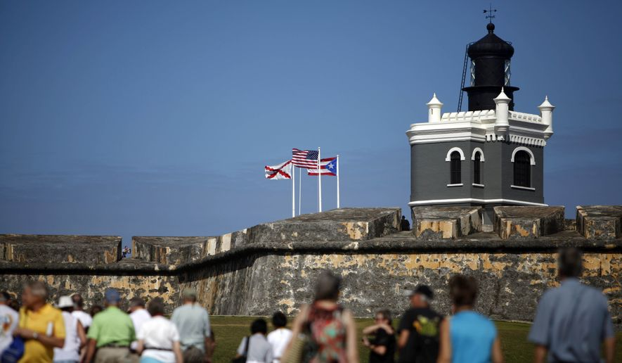 """SAN JUAN P.R. -Tourists walk near the 16th century Spanish fort called El Morro in Old San Juan, Puerto Rico. There's an entrance fee to enter the Castillo San Felipe del Morro, but the best way to enjoy this U.S. National Historic Site requires no money at all. The fort that towers over San Juan Bay, known universally as just """"El Morro,"""" is a great place to stroll, especially at sunset. The massive rolling expanse of grass at the foot of the fort has spectacular views in any direction. It's a popular place to picnic and fly a kite, sold by nearby street vendors. (AP Photo/Ricardo Arduengo, File)"""
