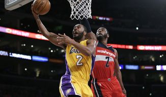 Los Angeles Lakers' Wayne Ellington, left, goes up for a basket past Washington Wizards' John Wall during the first half of an NBA basketball game, Tuesday, Jan. 27, 2015, in Los Angeles. (AP Photo/Jae C. Hong)