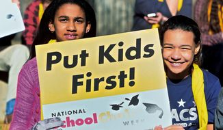 """Students Isabel Onisile, 11, left, and Octavia McKindra, 11, attend a rally at the Sierra Nevada Academy Charter School at the National School Choice Week Capitol celebration in Carson City, Nev., on Wednesday, Jan. 28, 2015. An estimated 500 students, parents and teachers, many wearing bright yellow scarves and carrying signs that said """"I trust parents"""" gathered near the Capitol in Carson City on Wednesday to show their support for measures that would make it easier for families to move their children to charter or private schools. (AP Photo/Nevada Appeal, Brad Coman)"""