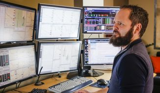 In this Jan. 22, 2015 photo, oil trader Justin Thomas looks at his computer screens at his one-person office in Boise, Idaho. Thomas is one of thousands of oil traders around the world who have helped turn market fundamentals, lots of oil and not much demand, into a plunge in the price of crude. (AP Photo/Otto Kitsinger)