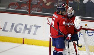 Washington Capitals left wing Alex Ovechkin (8), from Russia, celebrates with goalie Braden Holtby (70) after an NHL hockey game against the Pittsburgh Penguins, Wednesday, Jan. 28, 2015, in Washington. The Capitals won 4-0. (AP Photo/Alex Brandon)