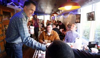 Former GOP presidential candidate Mitt Romney visits with diners at Little Dooey, a barbecue restaurant in Starkville, Miss., Wednesday, Jan. 28, 2015. (AP Photo/Rogelio V. Solis)