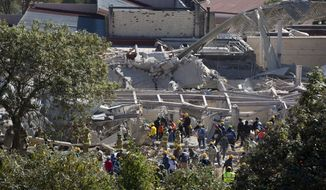 Rescue workers comb through the rubble where a gas truck exploded at a maternity and children's hospital in Cuajimalpa, a Mexico City borough, Thursday, Jan. 29, 2015. A powerful gas tank truck explosion shattered the hospital on the western edge of Mexico's capital, killing at least three adults and one baby and injuring dozens. (AP Photo/Rebecca Blackwell)