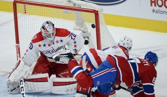 Montreal Canadiens left wing Max Pacioretty (67) scores the game-winning goal past Washington Capitals goalie Braden Holtby (70) and Capitals defenseman Matt Niskanen (2) during the overtime period of an NHL hockey game Saturday, Jan. 31, 2015,  in Montreal. The Canadiens won 1-0. (AP Photo/The Canadian Press, Ryan Remiorz)