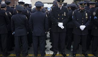 FILE - In this Jan. 4, 2015 file photo, some police officers, left, turn their backs in a sign of disapproval as Mayor Bill de Blasio remaks are transmitted on a large video screen during the funeral of New York Police Department Officer Wenjian Liu outside of a funeral home in the Brooklyn borough of New York. Mayor Bill de Blasio declares he has moved past the crisis with police that threatened to derail his administration. He says in an interview with The Associated Press that he was able to pull off the feat sticking to a strategy to maintain the moral high ground and avoid confrontation with police unions. At the same time, public opinion turned against police for their behavior in the feud, including turning their backs on the mayor. (AP Photo/John Minchillo, File)