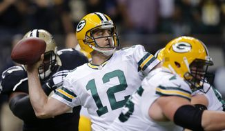 FILE - In this Oct. 26, 2014 file photo, Green Bay Packers quarterback Aaron Rodgers throws a touchdown pass during the first half of an NFL football game against the New Orleans Saints in New Orleans. Rodgers has won his second Associated Press NFL Most Valuable Player award. (AP Photo/Bill Haber, File)