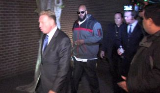 """FILE - In this Friday, Jan. 30, 2015 file image from video, Death Row Records founder Marion """"Suge"""" Knight, right, walks into the Los Angeles County Sheriffs department in the early morning in connection with a hit-and-run incident that left one man dead and another injured. Knight, had his $2 million bail revoked in Los Angeles after his arrest in running down and killing a man. Los Angeles County sheriff's spokeswoman Nicole Nishida says detectives asked a bail commissioner Monday, Feb. 2, 2015, to keep Knight behind bars because he is a possible flight risk.  (AP Photo/OnSceneVideo via AP Television, File)"""