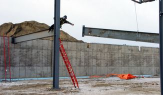 In this Wednesday, Jan. 14, 2015, photo, a worker reaches for a steel beam during construction of a new high school and civic center in Watford City, N.D. An oil boom that's drawn thousands of workers to the region has stretched public services to their limits, and drilling is expected to continue despite the recent sharp drop in oil prices. (AP Photo/Matthew Brown)