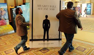 "Sheldon Domke (left) and Adam Mast move an advertisement for the upcoming film ""Fifty Shades of Grey"" during the second day of CinemaCon 2014 in Las Vegas. (Associated Press)"