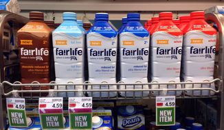 In this Friday, Jan. 23, 2015, photo, Fairlife milk products appear on display in the dairy section of an Indianapolis grocery store. Fairlife, which is rolling out nationally in coming weeks, is the product of a joint venture between Select Milk Producers, a dairy cooperative, and Coca-Cola. The product is filtered to have more protein and less sugar than regular milk. (AP Photo/Michael Conroy)