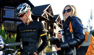In this Aug. 25, 2012, file photo, Lance Armstrong, left, prepares to take part in the Power of Four mountain bicycle race, as his girlfriend Anna Hansen looks on, in Snowmass Village, Colo. Authorities say the disgraced cyclist hit two parked cars after a night of partying in Aspen but agreed to let his girlfriend take the blame to avoid national attention. (AP Photo/David Zalubowski, File)
