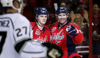 Washington Capitals left wing Andre Burakovsky (65), from Austria, and right wing Troy Brouwer (20) celebrate Brouwer's goal during the first period of an NHL hockey game against the Los Angeles Kings, Tuesday, Feb. 3, 2015, in Washington. (AP Photo/Alex Brandon)